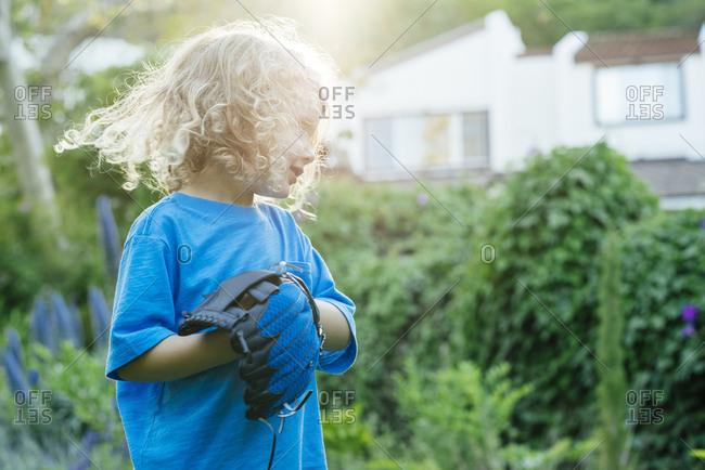 Cute boy wearing baseball glove in yard during sunny day