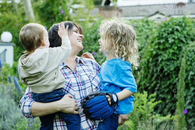 Happy mature woman carrying sons in yard during sunny day