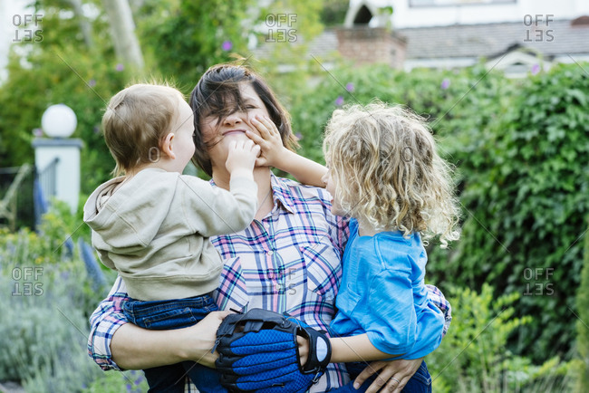 Boys touching mother's face in yard during sunny day