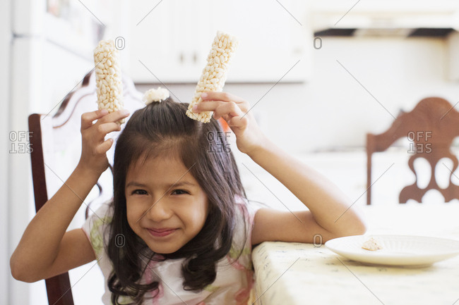 Girl holding snack above her head
