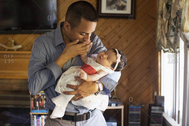 Father holding and kissing his baby