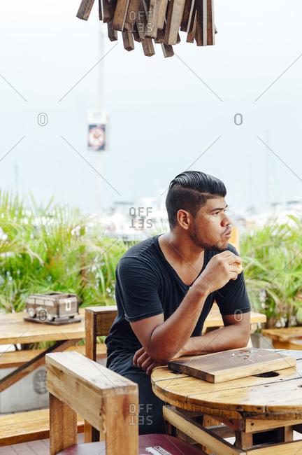 Hispanic Latin male customer eating burger at restaurant