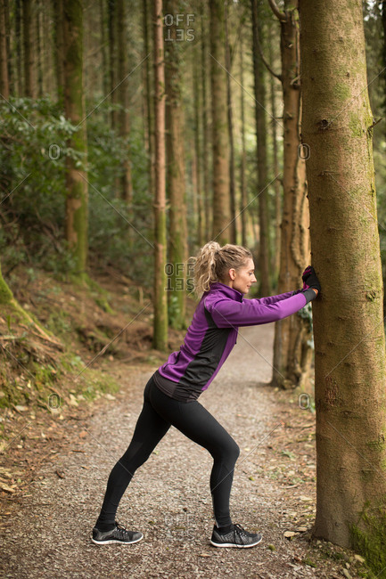 Woman performing stretching exercise in forest