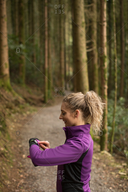 Beautiful woman using smart watch in the forest