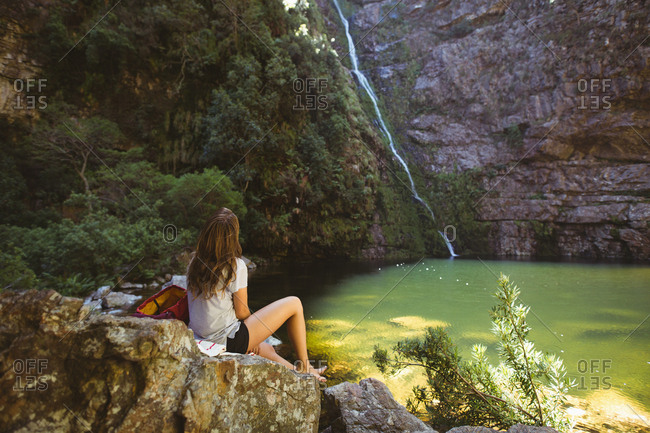 Woman looking at the waterfall in countryside