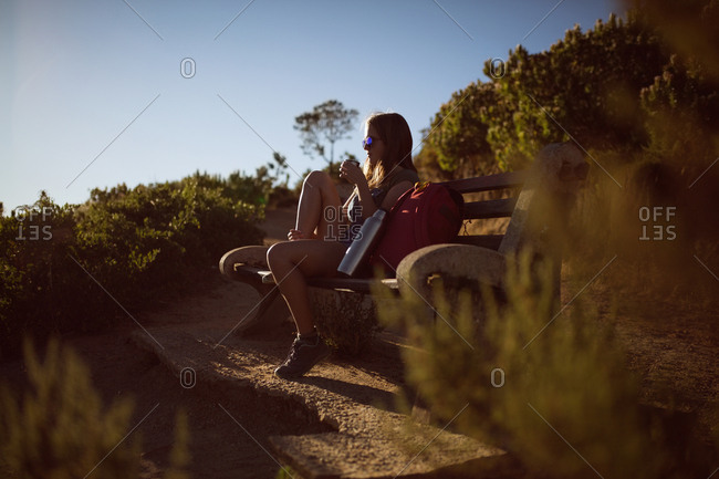 Woman sitting on bench and having coffee in countryside