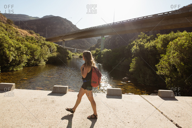 Female hiker walking near the river on a sunny day