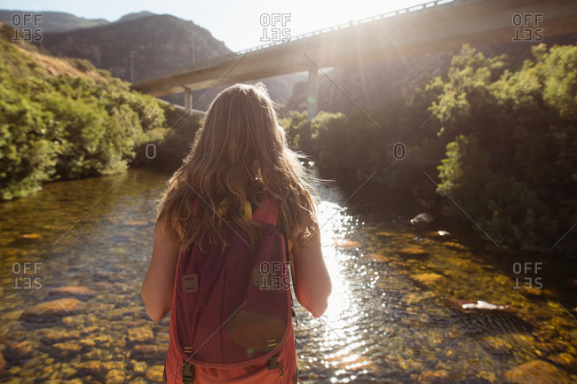 Rear view of female hiker looking at the river on a sunny day