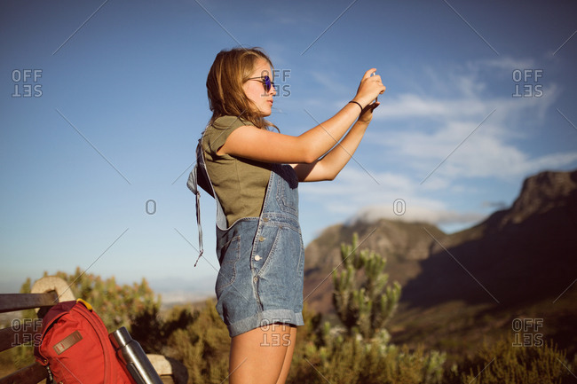 Young woman taking picture from mobile phone in countryside