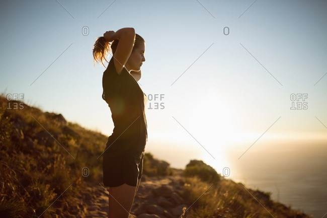 Young female hiker holding her hairs at countryside