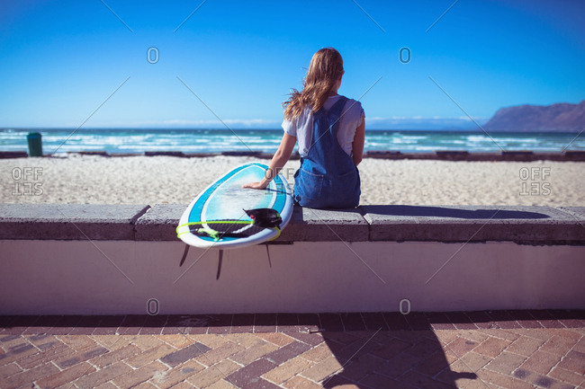 Rear view of female surfer sitting with surfboard and looking at the sea