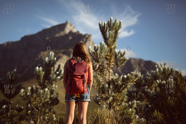 Woman standing with backpack in countryside in countryside on a sunny day