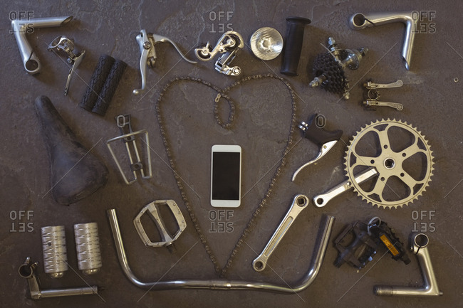 Overhead view of mobile phone amidst bicycle parts on floor at workshop