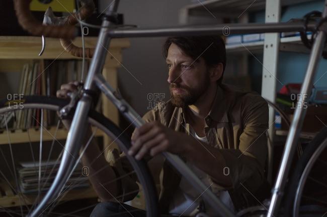 Employee repairing vintage bicycle at workshop