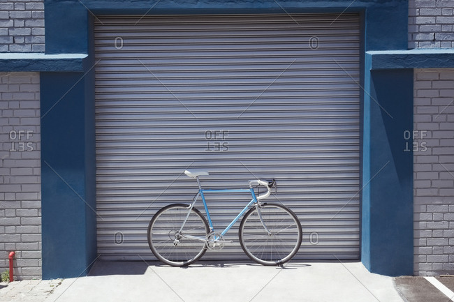 Vintage bicycle parked by closed workshop during sunny day