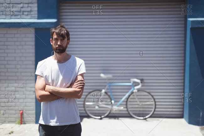 Portrait of employee standing with bicycle parked by workshop in background during sunny day