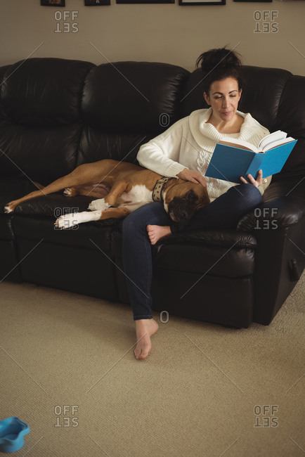 Woman reading a novel while dog relaxing on her lap in living room