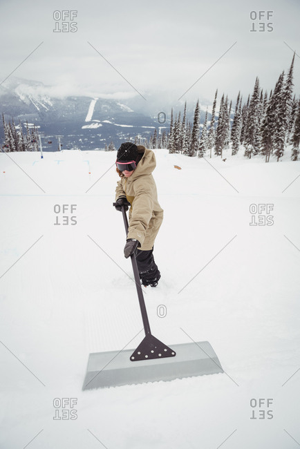 Man cleaning snow in ski resort during winter