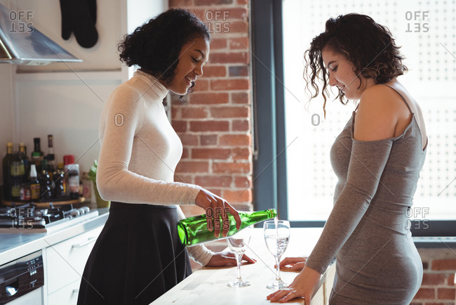 Lesbian couple pouring wine in glass in the kitchen