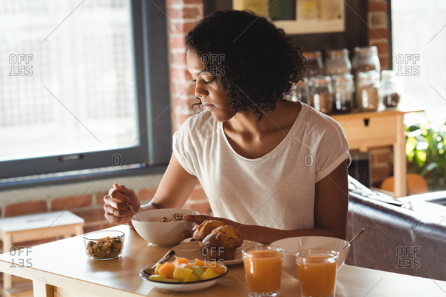 Woman having breakfast while sitting on the table at home