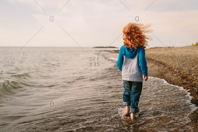 Boy walking through surf on a pebble beach