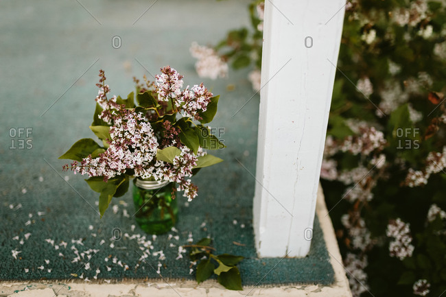 Lilac flowers arrange in a glass canning jar on a porch