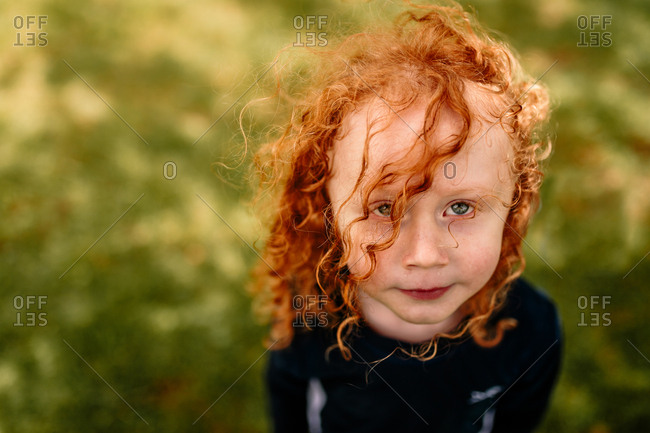 Boy with long red, curly hair standing outside