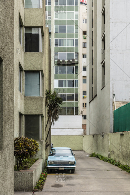 Lima, Peru - August 7, 2016: Classic car parked on a side street near modern buildings in Lima, Peru