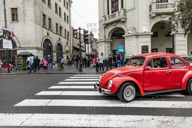 Lima, Peru - August 7, 2016: Classic car driving through an intersection in Lima, Peru