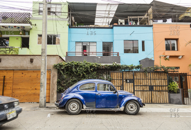 Lima, Peru - August 8, 2016: Classic car parked on the street in front of colorful buildings in Lima, Peru