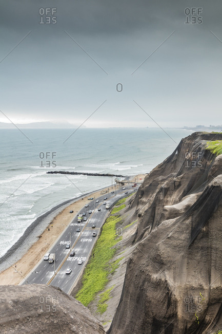 Lima, Peru - August 8, 2016: Material covering cliffs beside an ocean highway in Lima, Peru