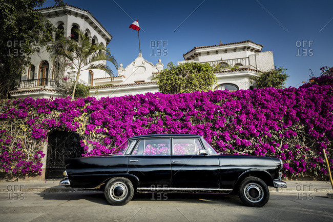 Lima, Peru - August 9, 2016: Classic car parked outside of a mansion with flower-covered walls in Lima, Peru