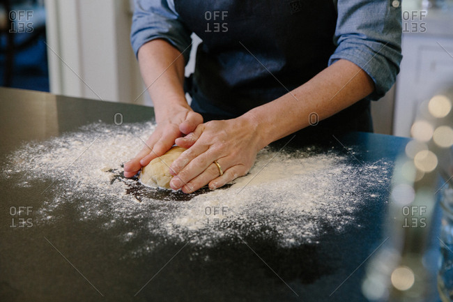 Chef kneading dough on floured counter