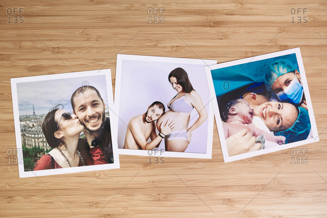 Arrangement of three family pictures of pregnancy and delivery on a bamboo wooden table