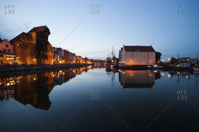 Poland - Gdansk - lighted row of houses with crane gate at Motlawa bank at dusk