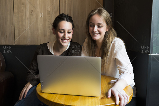 Two smiling friends sitting in a coffee shop looking at laptop