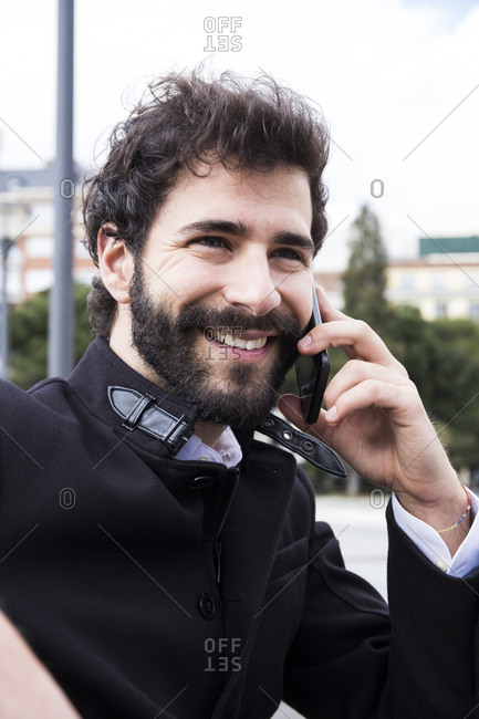 Portrait of smiling young man with full beard on the phone