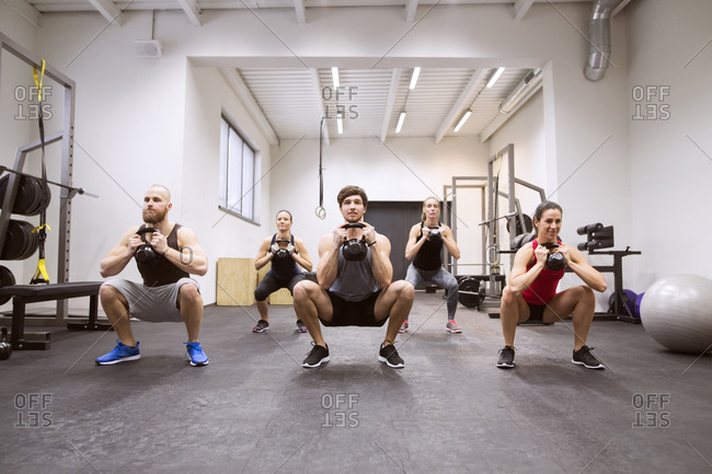 Group of athletes exercising with kettlebells in gym