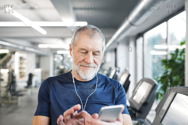 Senior man with smartphone and earphones in gym