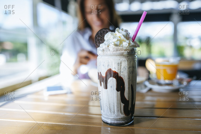 Glass of chocolate milkshake with cream on table