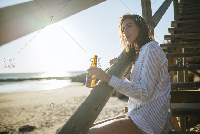 Young woman with bottle of beer relaxing on the beach at sunset