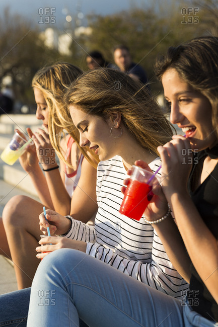 Three young women with soft drinks at sunset