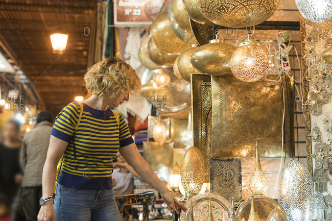 Morocco - woman at a shop with lamps