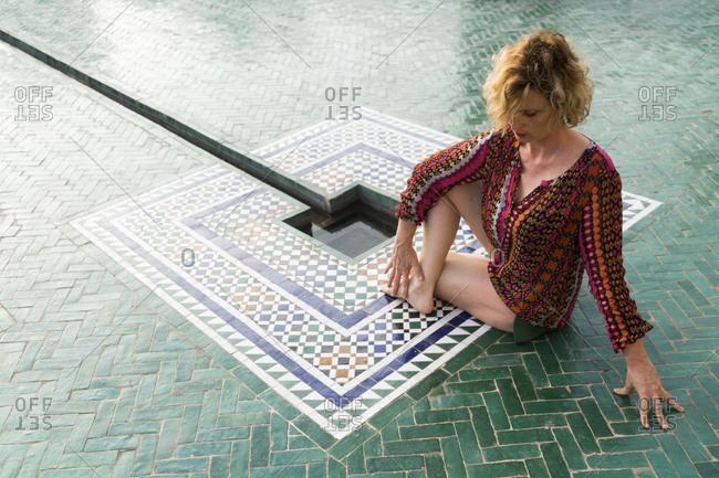 Morocco - Marrakesh - tourist sitting on the floor doing yoga