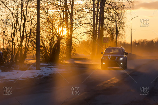 Car on road in winter at sunset