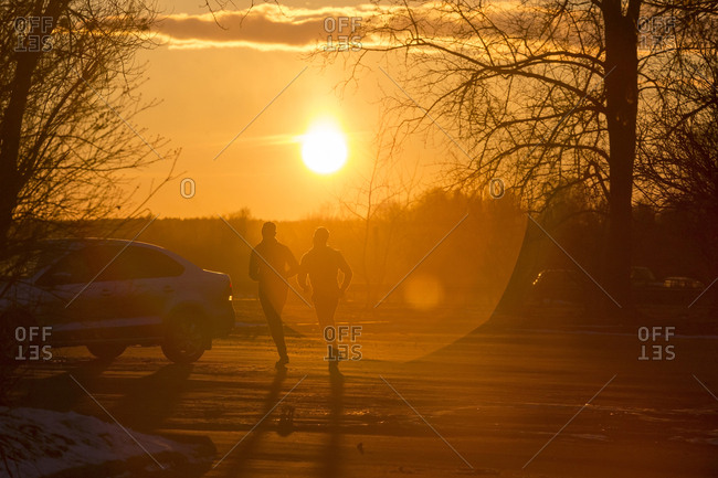Silhouette of two joggers in winter at sunset