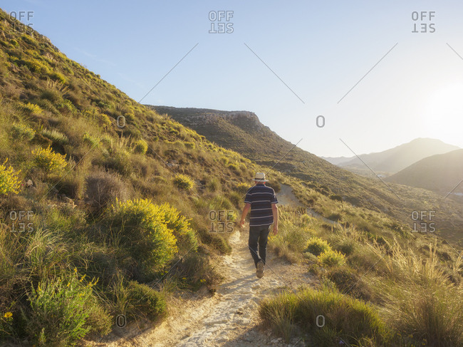 Spain - Andalusia - Cabo de Gata - back view of man hiking