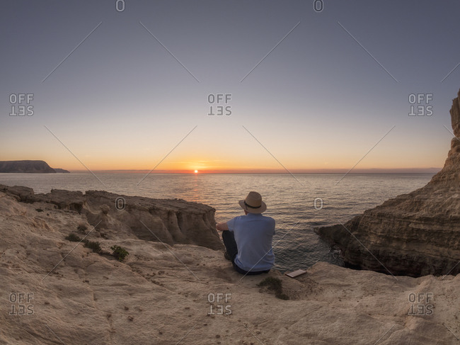 Spain - Andalusia - Cabo de Gata - back view of man looking at the sea at sunrise