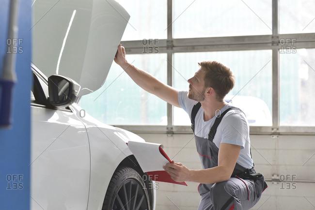 Car mechanic in a workshop examining car