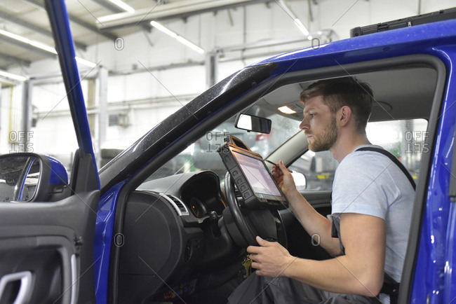Car mechanic in a workshop using diagnostics computer in car